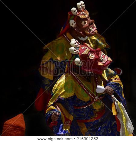 Buddhist monks in the ancient red masks of Mahakala with formidable faces and in festive bright clothes during a mystical ritual in the monastery of Karsh, Zanskar.