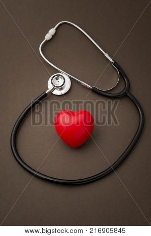 Stethoscope Around A Red Rubber Heart On White Background