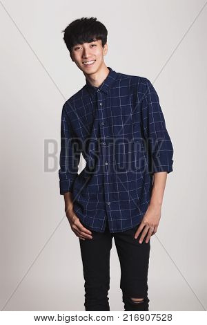 Studio portrait of Asian young man with happy smile and looking at camera