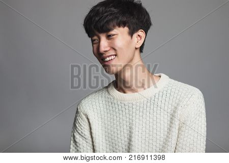 Studio portrait of Asian man looking sideways with confident smile