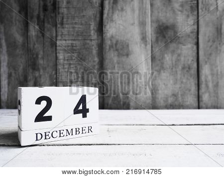 December 24th. White wooden block calendar show date 24 and month December on wood background with copy space. Christmas Eve.