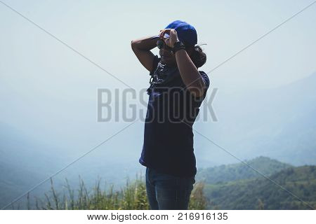 Asian man travel relax in the holiday. Stand and watch landscape on the Moutain. Mountain Park happily. In Thailand