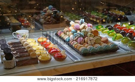 Sydney, Australia - November 03, 2017: Cakes in showcase. Australian pastry shop with different cookies macaroons jelly cakes with fruits and berries.