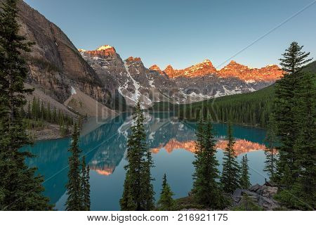 Beautiful Sunrise under turquoise waters of the Moraine lake in Rocky Mountains, Banff National Park, Canada.
