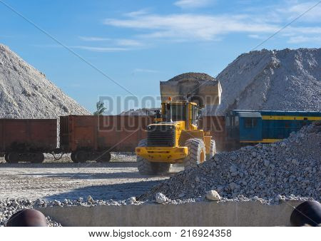 bucket loader loads the unique blue clay in railway cars