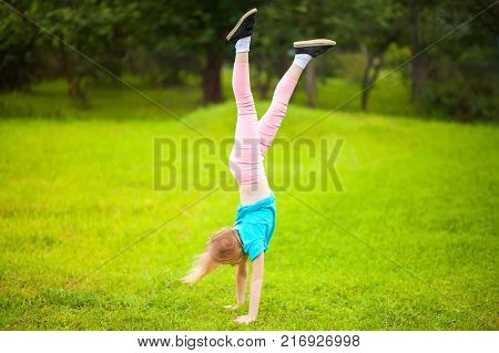 Active Little School Girl Somersault Outdoors.