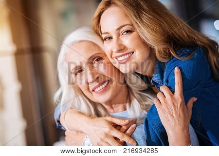 Close relatives. Positive attentive woman showing her respect and love to a kind loving grandmother while hugging her