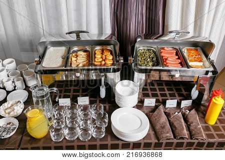 Many buffet heated trays ready for service. Breakfast in hotel catering buffet, metal containers with warm meals.