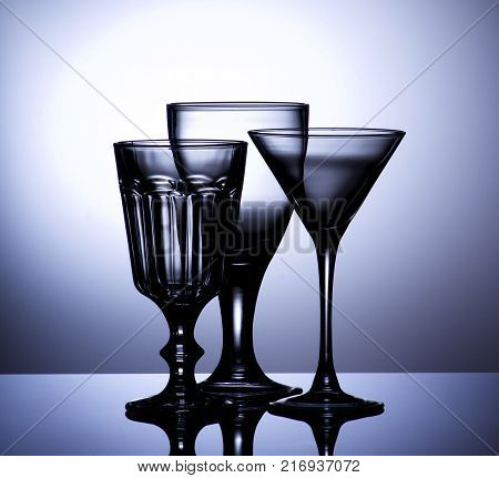 Three Various Empty Wine Glasses for Wine and Martini with Reflection on Glass and Shadow Backlight. Grapfite Toned