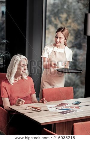 Helpful waitress. Cheerful calm pleasant waitress standing with a tray and giving a cup of tasty coffee to a busy friendly senior woman while beautiful bright color palettes being placed on the table poster