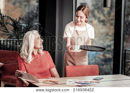 Your order. Kind attentive young waitress smiling while standing with a tray and giving coffee to a senior positive woman in a red blouse
