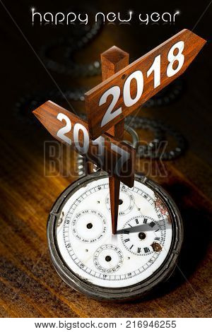 Happy New Year 2018 - Old pocket watch with two wooden signs with arrows and the years 2017 and 2018