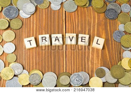 Word TRAVEL on wooden cube with coins frame at wood background.Financial concept,