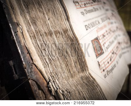 detail of the pages of a church choir books on a wooden lectern. Very old deteriorated books 16th century, vintage