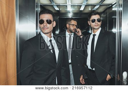bodyguard obstructing paparazzi when celebrity going into elevator poster