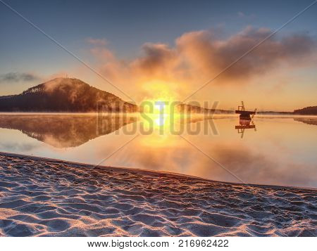 Abandoned Baby Swing On Sandy Beach Of Lake. Cold Morning After Season In Holiday Resort.