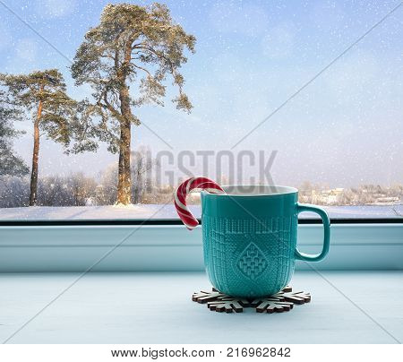 Winter still life - cup with candy cane on windowsill and winter forest landscape outdoors. Winter cozy still life with concept of spending winter time indoors. Winter composition. Winter still life with Christmas mood
