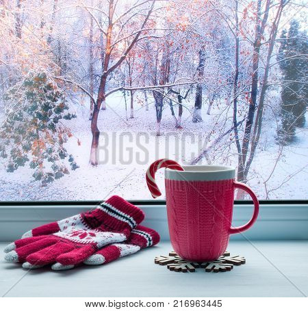 Winter still life. Cup with candy cane and woolen gloves on windowsill and winter forest outdoors, winter background. Festive winter still life, spending winter time at home concept. Winter composition. Festive winter card
