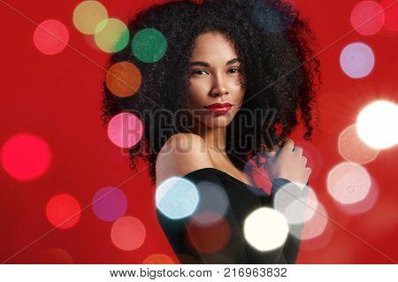 black woman with big afro hair and christmas holiday bokeh lights around