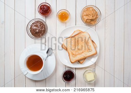 A white cup of black tea with Sandwiches or toasts with peanut butter, chocolate paste and strawberry, currant and apricot jelly or jam on white wooden table, top view, flat lay, Breakfast concept