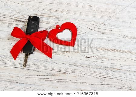 valentine's day or christmas car key gift. Car key with a red ribbon and heart on white wooden table.