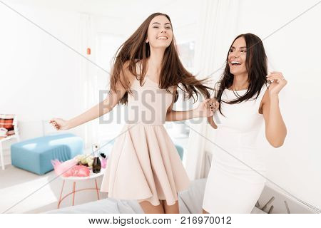Pre-wedding care. Girls at a hen-party. Girls in a veil are jumping on the bed. They have fun in a bright room.