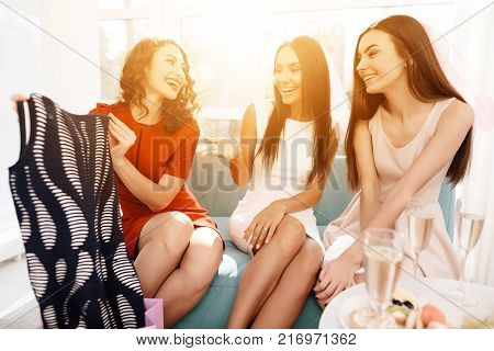 Girls have a great time at the hen-party. Three girls in dresses are having fun in a bright room. Bridesmaids and bride celebrating. Girls choose dresses for bridesmaids.