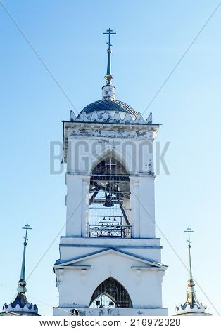 Bell tower from white brick with cross and bell in turn blue sky of the background