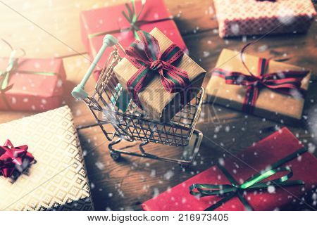 christmas gift shopping. wrapped present in shopping cart