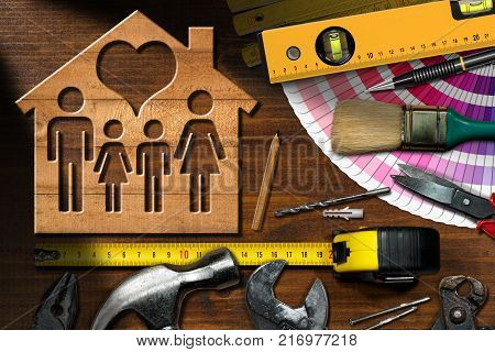 Home improvement concept - Wooden model house with a family and heart on a work table with tools