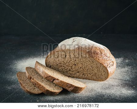 Sliced homemade sourdough rye bread with rye flour on black textured background. Copy space. Low key