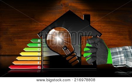 Energy Efficiency - Hand with work glove holding a model house (3D illustration) with energy efficiency rating and a light bulb. On a desk with reflections