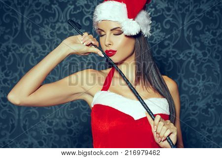 Sexy santa woman with red lips posing indoor with whip at Christmas bdsm