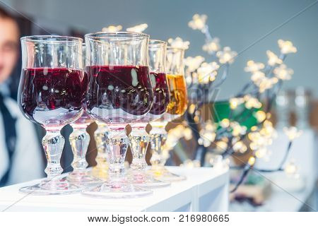 Catering table with alcoholic and non-alcoholic drinks on the business event in the hotel hall. Service at business meeting, party, weddings. Selective focus, space for text.