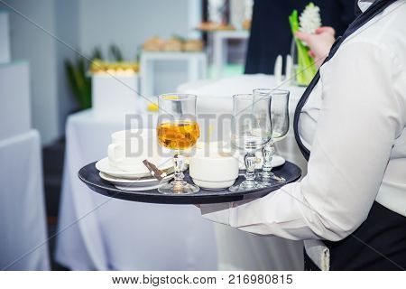 The waiter holding tray with dirty dishes after guests of the event. Catering Service at business meeting, party, weddings. Food Celebration Party Concept. Selective focus, space for text.