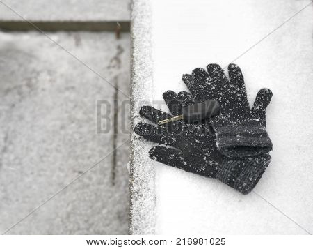Wool gloves and ignition key laid on the wooden bench covered with snow above view
