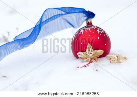 Red christmas toy: red Ball and wattle straw star and angel decor on snow. Winter holiday background