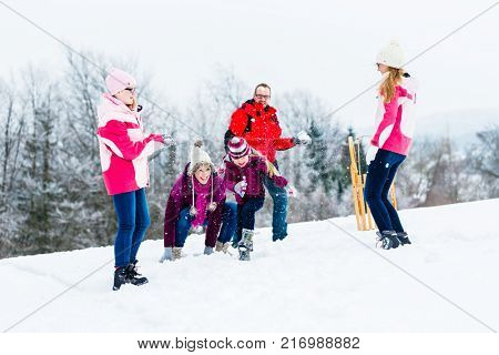 Family with kids having snowball fight in winter for fun