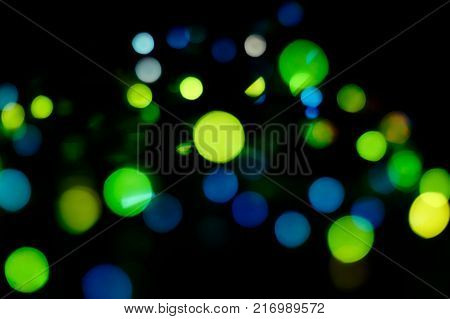 Christmas garland out of focus, Boke, green, blue and yellow circles on a black background, Christmas and new year