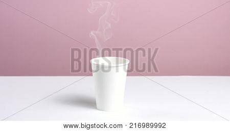 Hot water or coffee poured into a plain unlabeled paper cup on white table against pink wall, steam rising