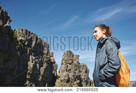 portrait of young woman hiker hiking in beautiful mountains. female hiker with small orange packpack black lava rocks background. excursion to the national park Thingvellir in Iceland