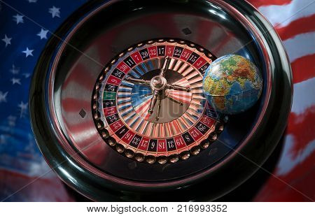 Globe on a roulette wheel on a background of the American flag
