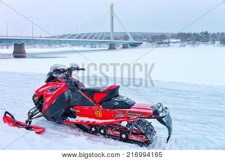 Rovaniemi Finland - March 2 2017: Red snowmobile on frozen lake at Candle bridge in winter Rovaniemi Lapland Finland