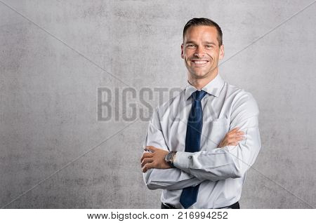 Happy businessman looking at camera on grey background with copy space. Handsome young business man standing against a grey wall with crossed arms. Successful formal man smiling with copy space.
