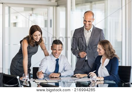 Happy business team in a meeting discussing about strategies in a modern board room. Businesspeople discussing the benefits of joint venture at office. Businessmen and businesswoman working together.