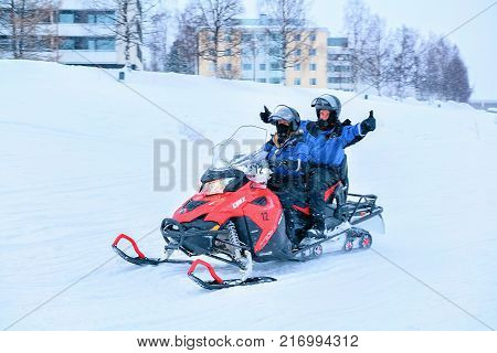 Rovaniemi Finland - March 2 2017: People waving hands and riding a snowmobile on the frozen lake in winter Rovaniemi Lapland Finland
