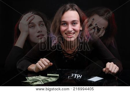 A girl is sitting at a table with cocaine and dollars with a smile with traces of cocaine on the nose on a black background