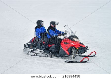 Rovaniemi Finland - March 2 2017: People riding a snowmobile on the frozen lake in winter Rovaniemi Lapland Finland