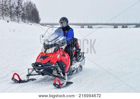 Rovaniemi Finland - March 2 2017: Man riding a snowmobile at the frozen lake in winter Rovaniemi Lapland Finland