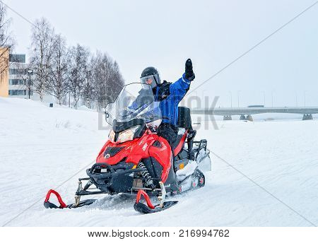 Rovaniemi Finland - March 2 2017: Man riding snowmobile and waving hand on the frozen lake in winter Rovaniemi Lapland Finland